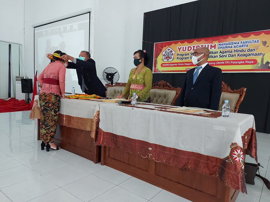 Pengalungan Medali oleh Dekan Fakultas Dharma Acarya (kiri) didampingi Kapodi Pendidikan Agama Hindu (tengah) dan Kaprodi Pendidikan Seni dan Keagamaan (Kanan)